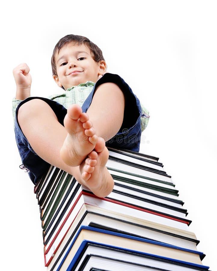 Un piccolo bambino sveglio e libri fotografia stock
