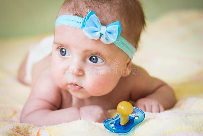 Un piccolo bambino tiene una tettarella in sua mano fotografia stock