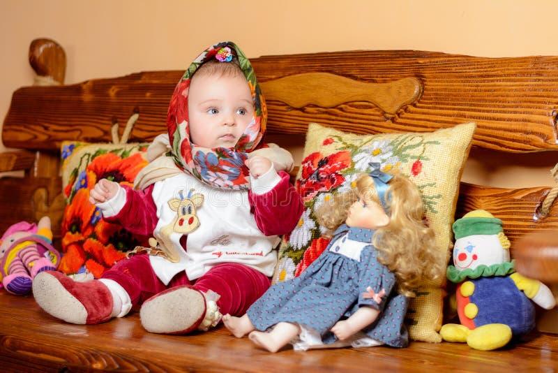 Un piccolo bambino in uno scialle che si siede su un sofà con i cuscini ricamati immagine stock libera da diritti