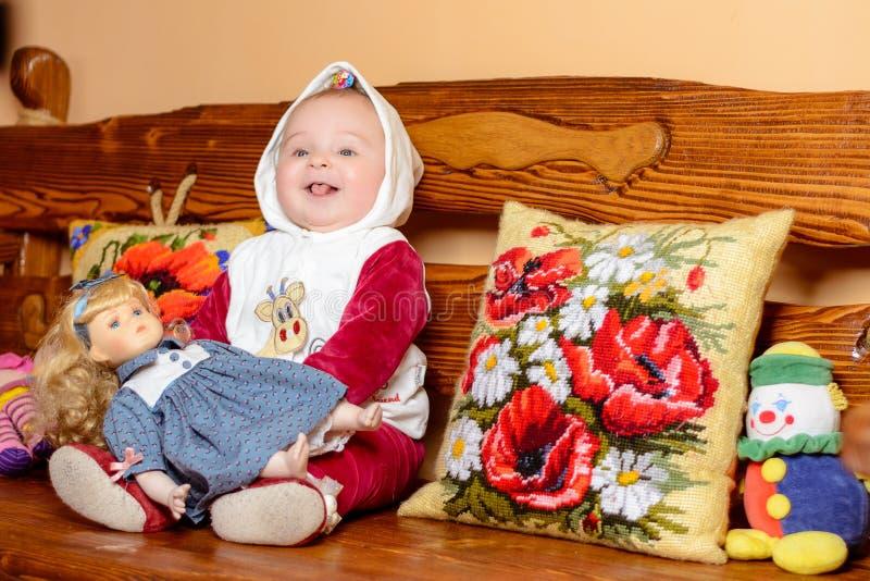 Un piccolo bambino in uno scialle che si siede su un sofà con i cuscini ricamati immagini stock