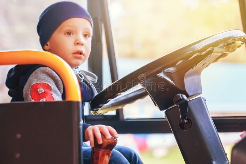 Un piccolo bello bambino che si siede nel bus e che gioca driver Front View fotografie stock libere da diritti