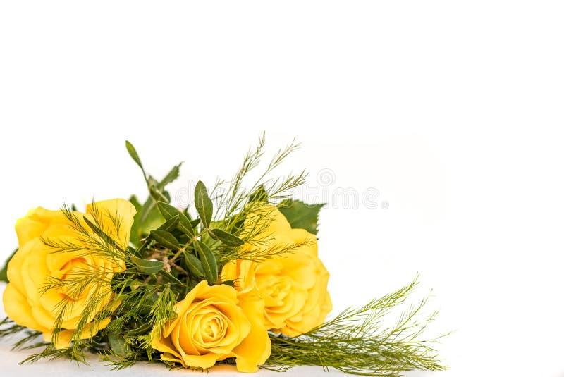 Un piccolo bouquet di tre rose gialle con fogliame verde immagine stock libera da diritti