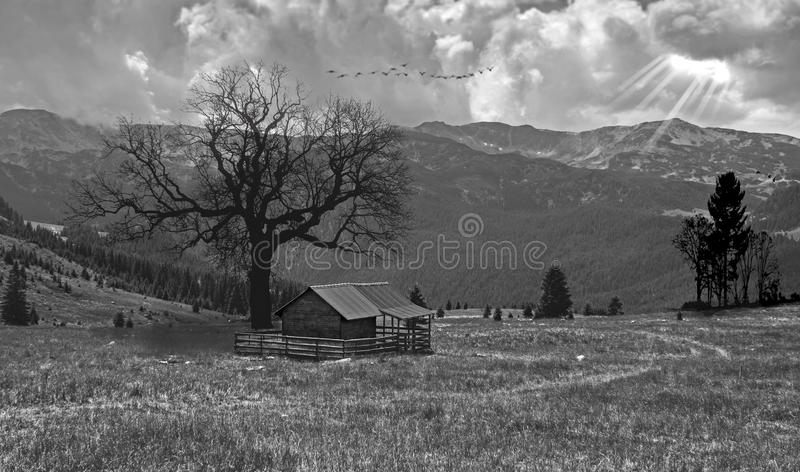 Un piccolo cottage di legno situato in un paesaggio misterioso, da qualche parte nel cuore delle montagne, vicino alla sera Un pa fotografia stock libera da diritti