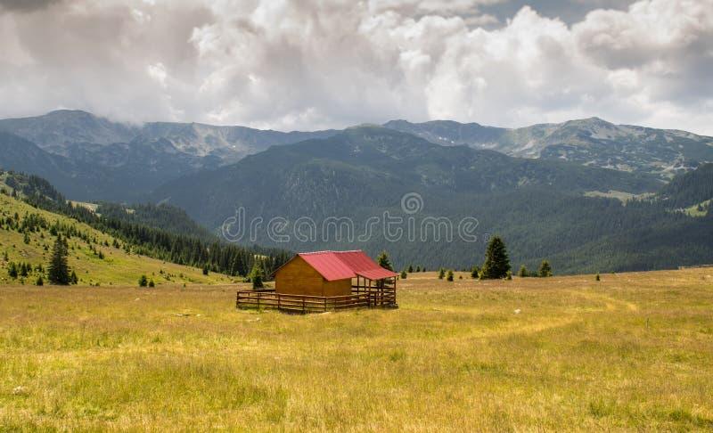 Un piccolo cottage di legno situato in un paesaggio di sogno, da qualche parte nel cuore delle montagne Una bella pianura verde c immagine stock libera da diritti