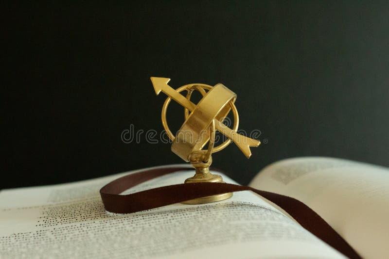 Un piccolo globo dell'astrolabio su un libro aperto come simbolo dello studio e della saggezza immagine stock
