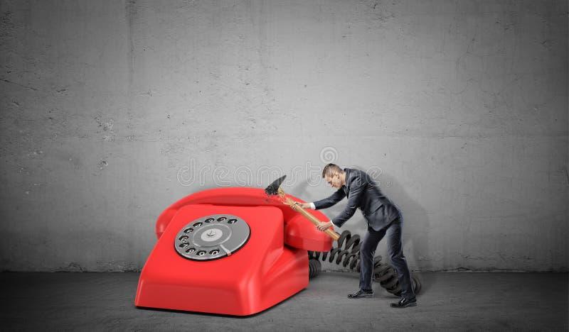Un piccolo imprenditore non riesce a distruggere un grande retro telefono rosso con un martello rotto fotografia stock libera da diritti