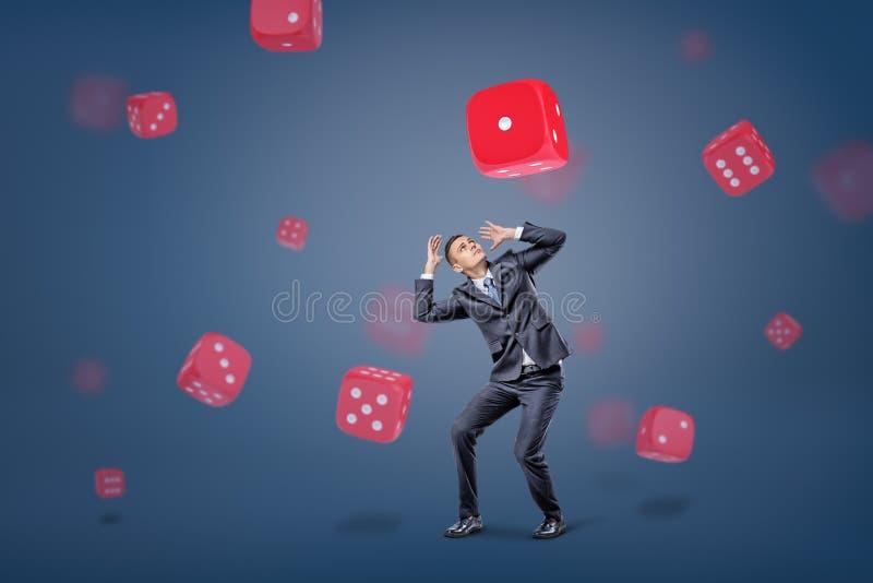 Un piccolo imprenditore si nasconde dal grande dado di gioco bianco e di rosso che cade su lui su un fondo blu immagine stock