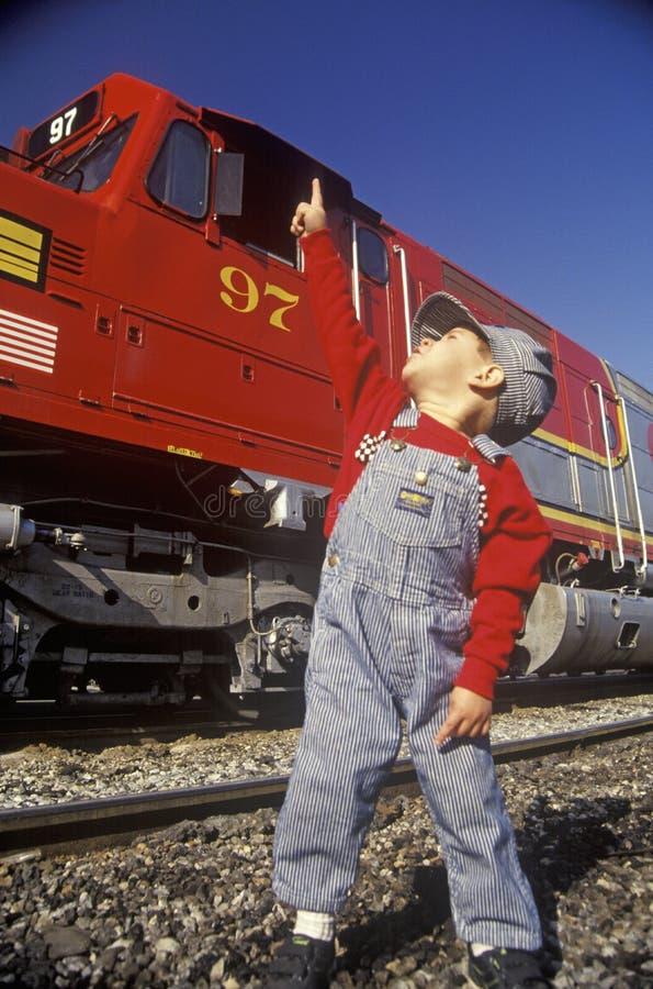 Un piccolo ingegnere in cappuccio dell'ingegnere con un treno storico di Santa Fe Diesel a Los Angeles, CA immagini stock libere da diritti