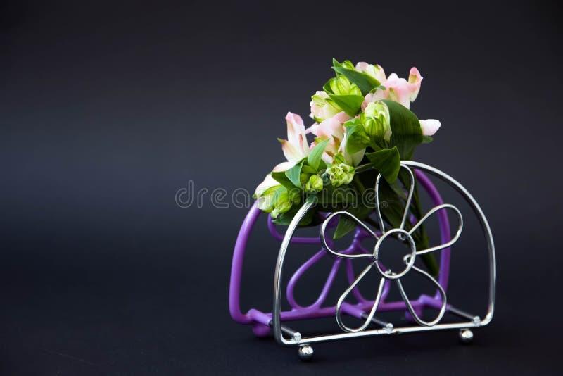 Un piccolo mazzo dei fiori, su un supporto lilla del tovagliolo su un fondo nero fotografia stock libera da diritti