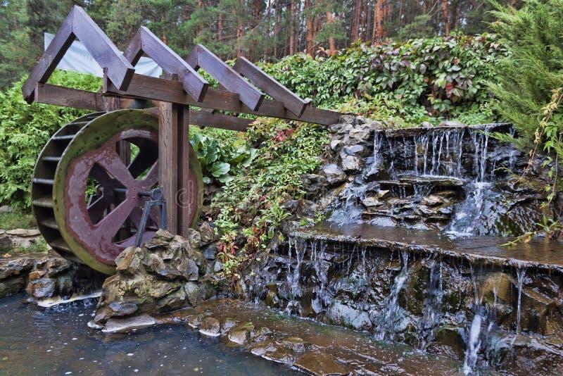 Un piccolo mulino a acqua accanto ad una piccola cascata artificiale fotografia stock