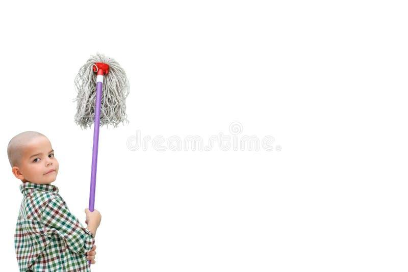 Un piccolo ragazzo calvo in una camicia di plaid sui supporti isolati bianchi di un fondo con una ZAZZERA in sue mani immagine stock libera da diritti
