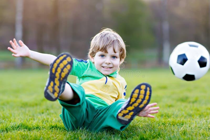 Un piccolo ragazzo sveglio del bambino di 4 che giocano a calcio con il calcio sul campo, all'aperto fotografie stock
