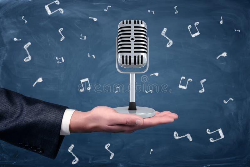 Un piccolo retro microfono d'argento che sta su una mano del ` s dell'uomo d'affari fra le note di musica attinte un fondo della  immagine stock