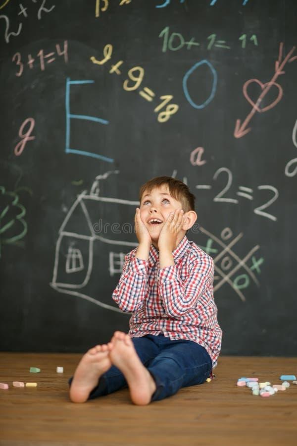 Un piccolo studente sui precedenti di un consiglio scolastico ha preso le sue mani sul suo fronte che posa un compito difficile immagini stock