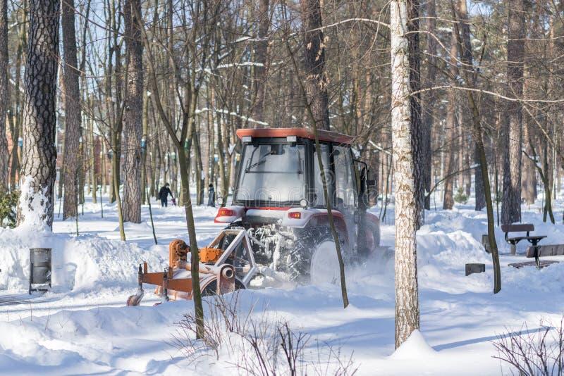 un piccolo trattore con una spazzola girante rimuove un'ampia strada nel parco della città dalla neve caduta fresca un chiaro gio immagini stock libere da diritti