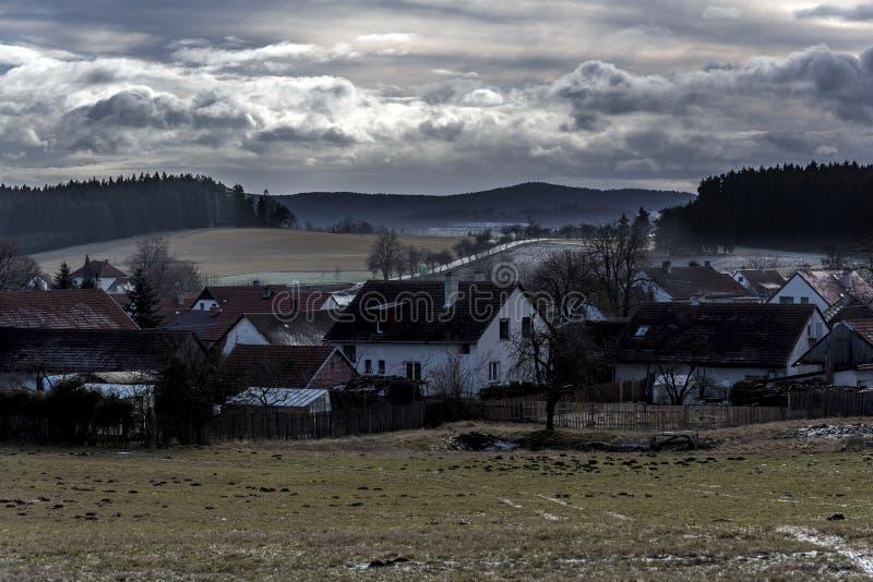 Un piccolo villaggio congelato nella valle fra i prati ed i campi fotografia stock