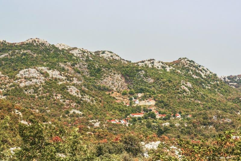 Un piccolo villaggio e costruzioni nelle montagne di Balcani verdi del Montenegro fotografie stock