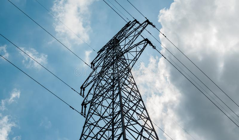 Un pilón de alto voltaje de la electricidad contra el cielo azul con las nubes en el día soleado Torre de alto voltaje de la tran imagenes de archivo