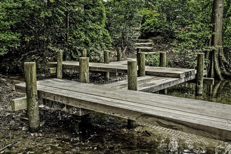 Un pilastro che quello conduce ad un percorso nel legno immagini stock libere da diritti