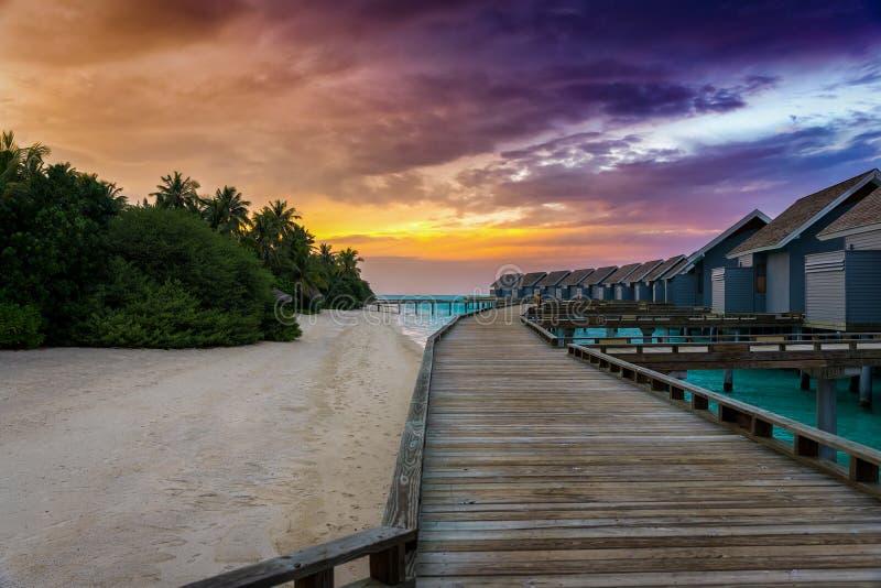 Un pilastro di legno che conduce per innaffiare le casette in Maldive fotografie stock libere da diritti