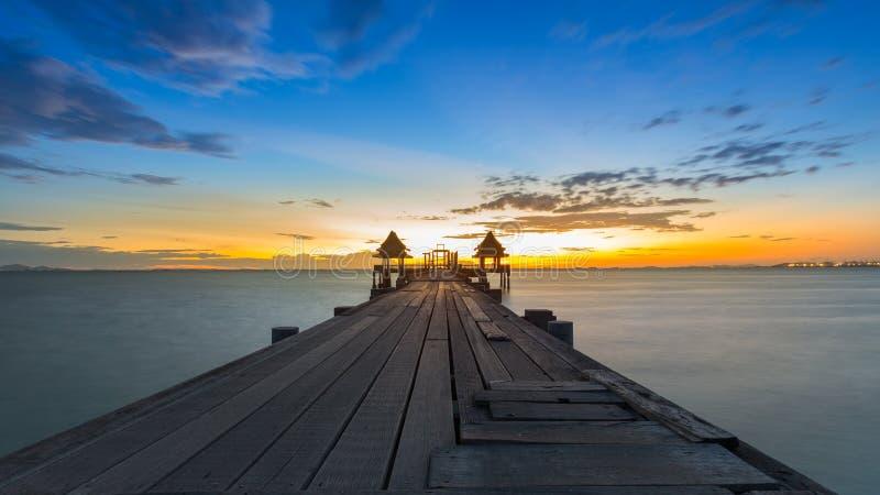 Un pilastro di legno lungo che conduce fuori sul mare durante il tramonto immagini stock libere da diritti