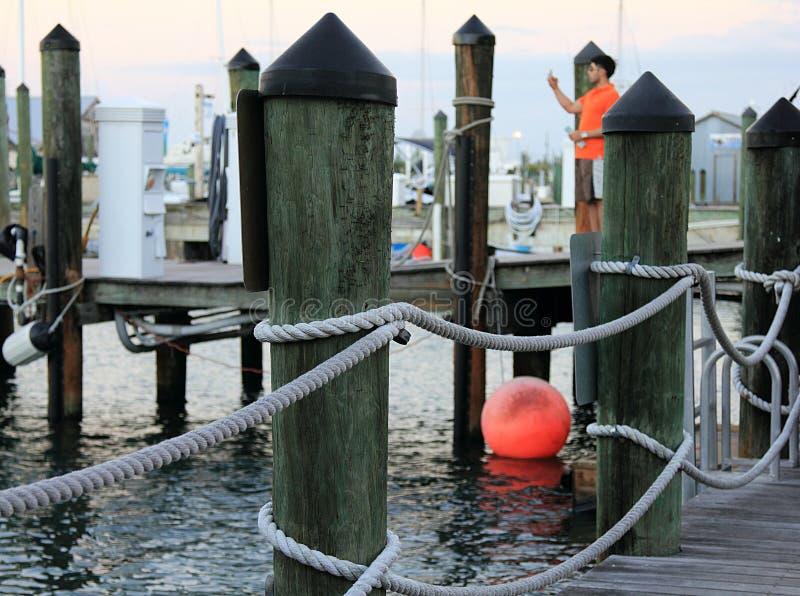 Un pilier à Key West, la Floride avec une balise orange et un type dans la chemise orange image stock