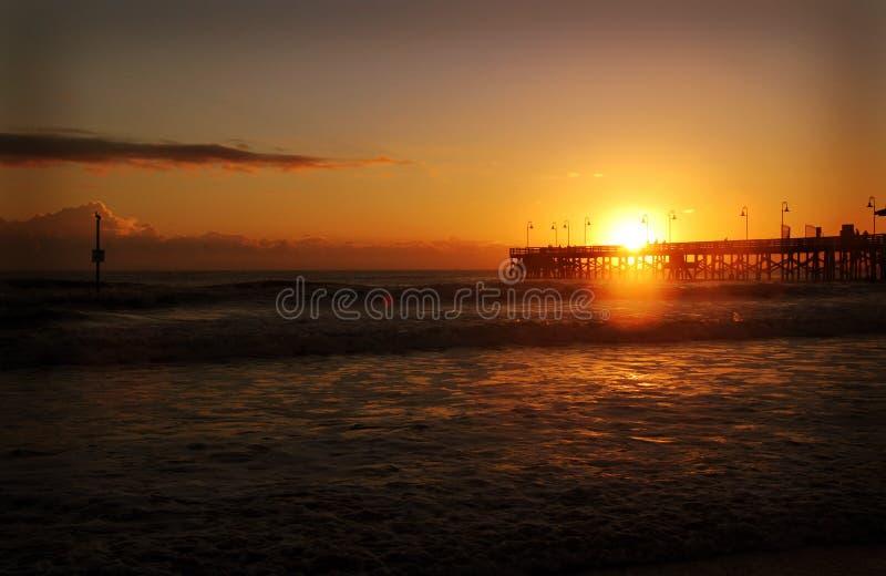 Un pilier par l'océan au lever de soleil photo stock