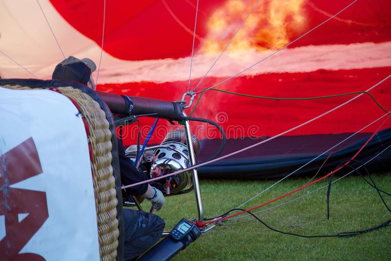 Un pilota del pallone brucia l'aria calda e gonfia il suo pallone per preparare per decolla fotografie stock