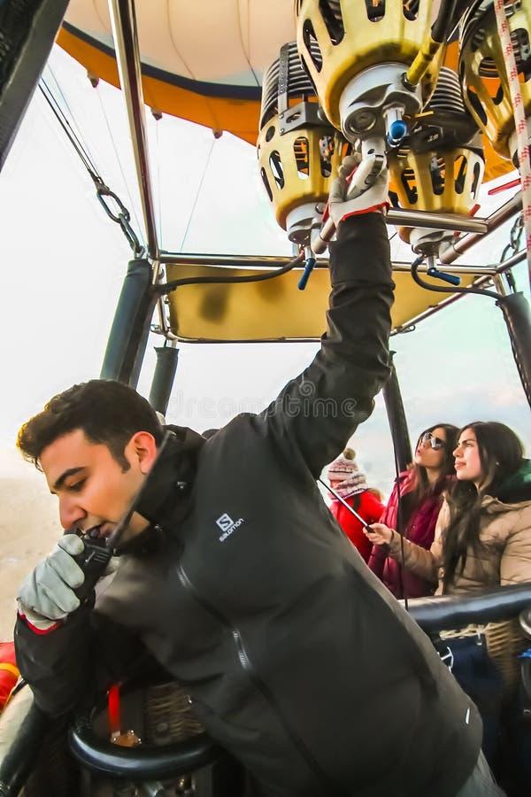 Un pilota della mongolfiera con una mano sul walkie-talkie e l'altra sul bruciatore immagini stock libere da diritti