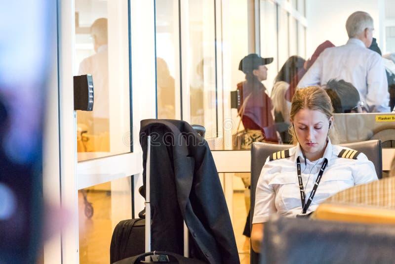 Un piloto de sexo femenino joven que espera su vuelo en el aeropuerto foto de archivo
