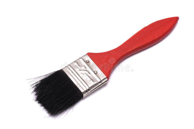 Un pinceau du ` s de décorateur avec la poignée rouge photos libres de droits