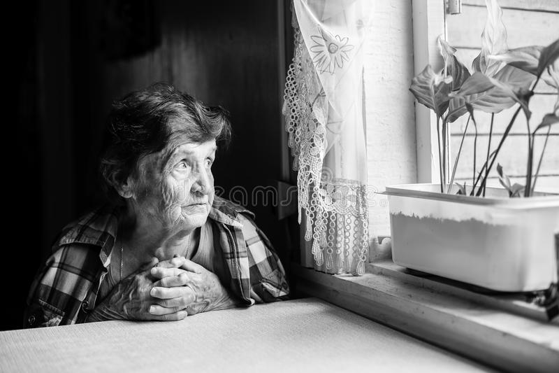 Un pining mayor de la mujer en la ventana fotografía de archivo libre de regalías