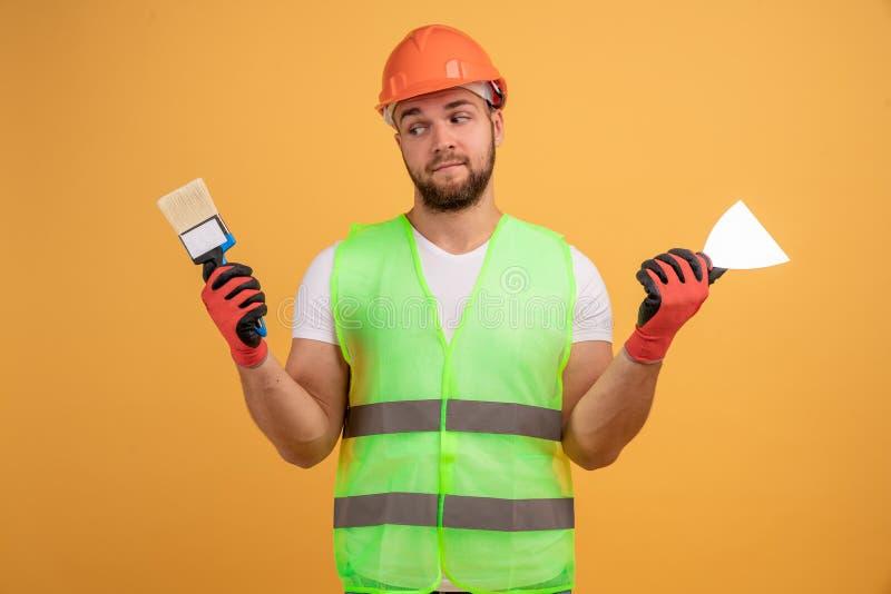Un pintor desconcertado sostiene pincel y espátula, lleva casco, posa con herramientas de construcción, ocupado en la reparación  imágenes de archivo libres de regalías