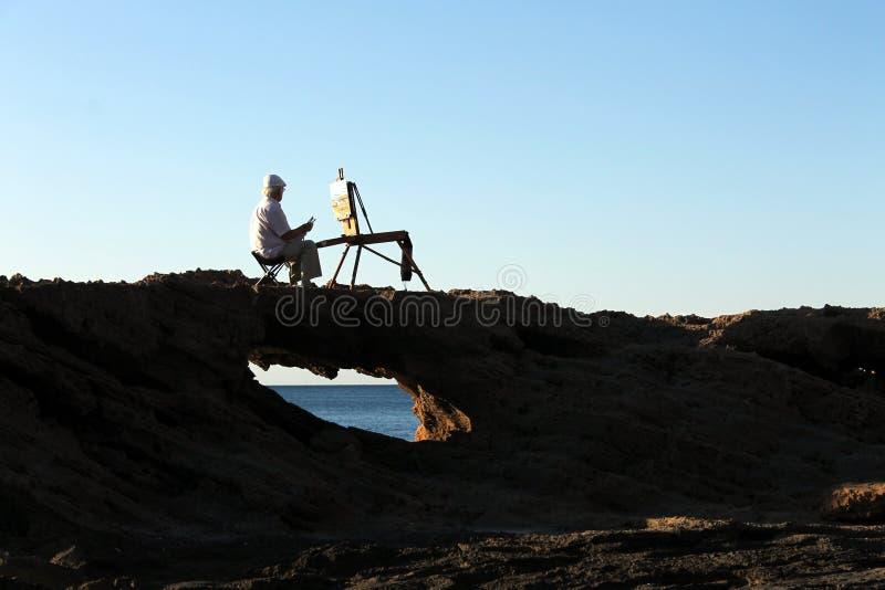 Un pintor que mira el horizonte del mar y que pinta una imagen sobre una roca en un lugar de la costa de Alicante en España foto de archivo