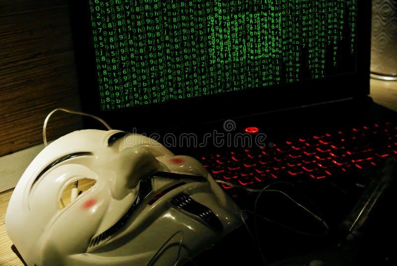 Un pirata informático anónimo intenta agrietar la protección del ` s del sistema operativo fotos de archivo
