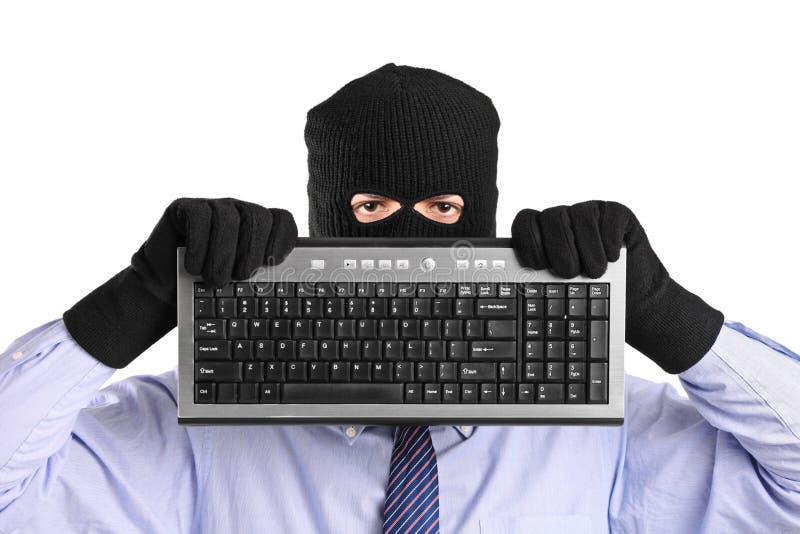 Un pirata informático con la máscara del robo que sostiene un teclado fotos de archivo