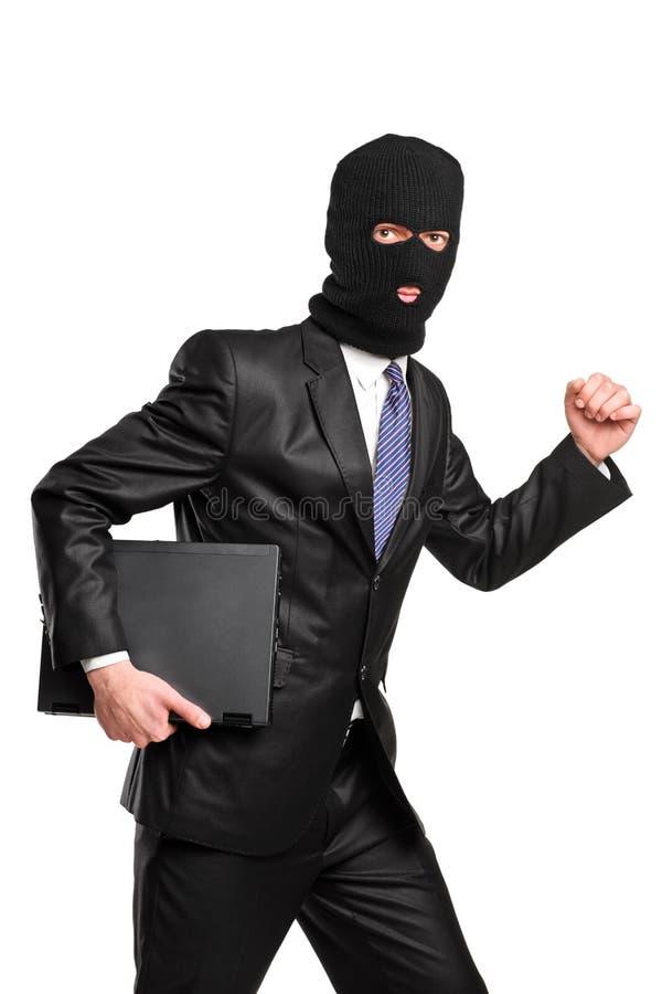 Un pirata informático en la máscara del robo que se ejecuta con la computadora portátil foto de archivo