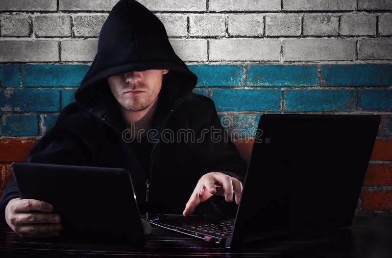 Un pirata informático que se sienta en un escritorio con un ordenador y una tableta en su mano imagen de archivo