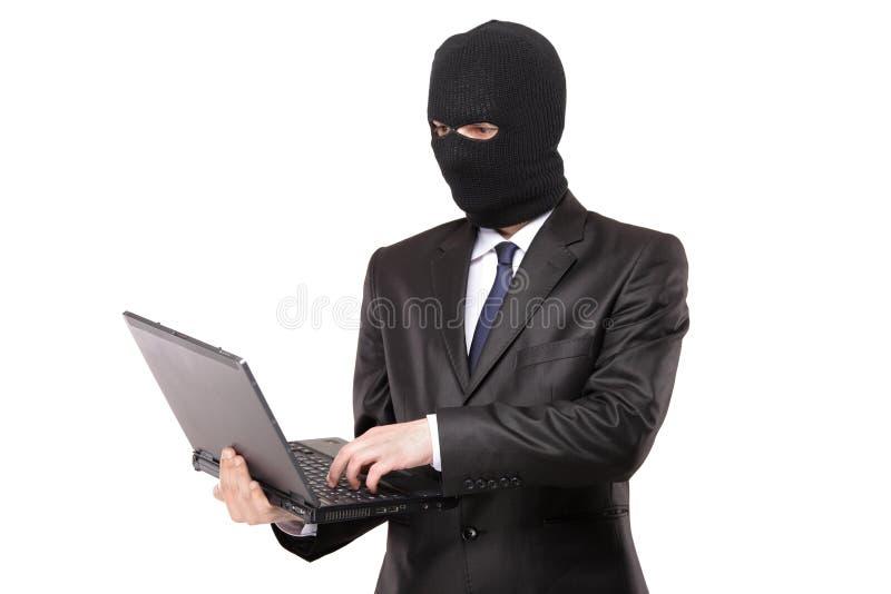 Un pirata informático que trabaja en una computadora portátil fotografía de archivo libre de regalías