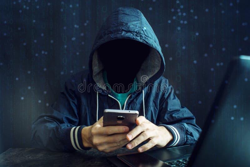 Un pirata informatico anonimo senza un fronte utilizza un telefono cellulare per incidere il sistema Il concetto del crimine cybe fotografia stock libera da diritti