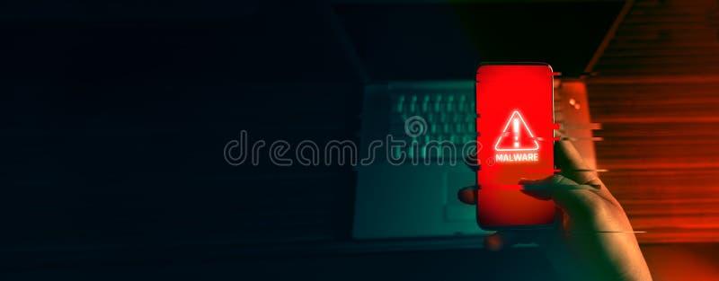 Un pirate informatique anonyme et utilisations un malware avec le téléphone portable d'entailler le mot de passe image libre de droits