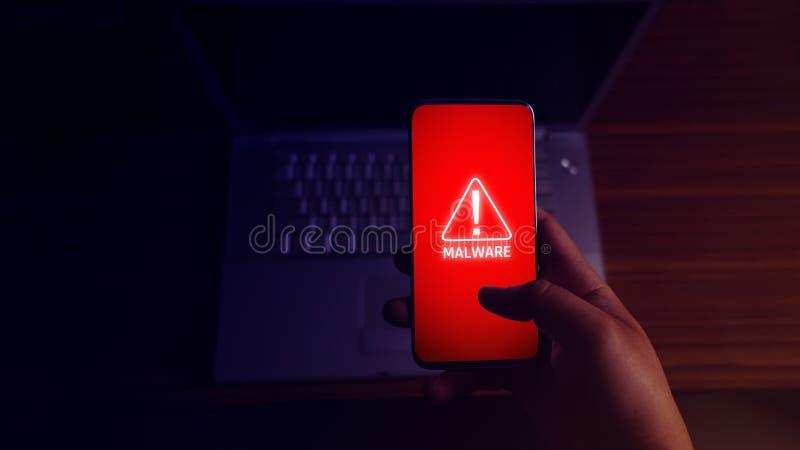 Un pirate informatique anonyme et utilisations un malware avec le téléphone portable d'entailler image stock