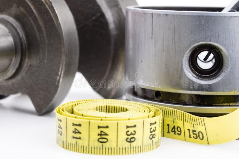 Un piston d'un moteur à combustion interne et un tailleur mesurent image stock