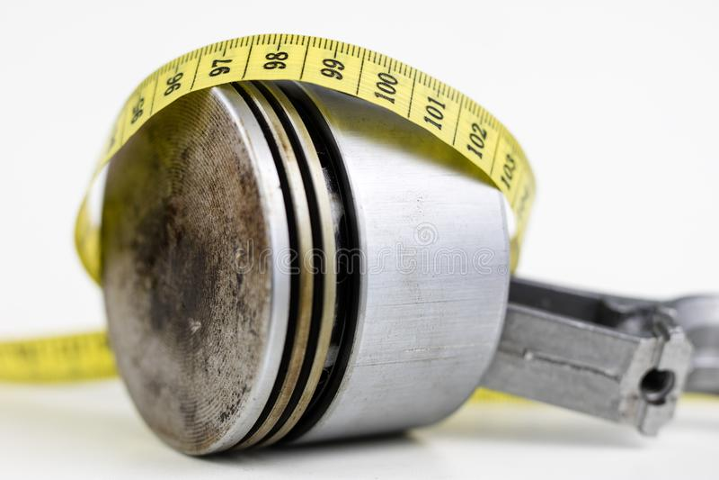 Un piston d'un moteur à combustion interne et un tailleur mesurent image libre de droits