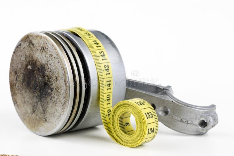 Un piston d'un moteur à combustion interne et un tailleur mesurent photos stock