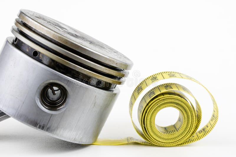 Un piston d'un moteur à combustion interne et un tailleur mesurent photo stock