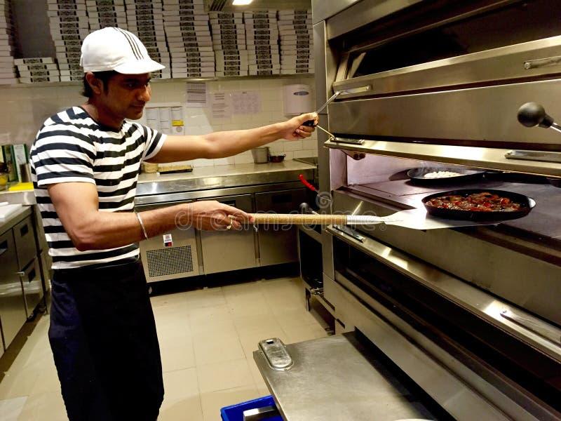 Un Pizzaiolo que saca una pizza de un horno de piedra imagen de archivo