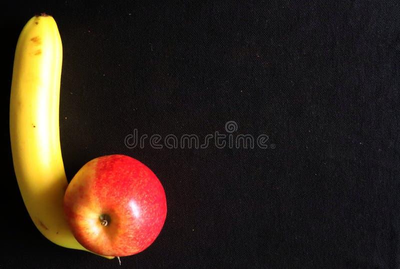 Un plátano y Apple contra fondo negro fotos de archivo