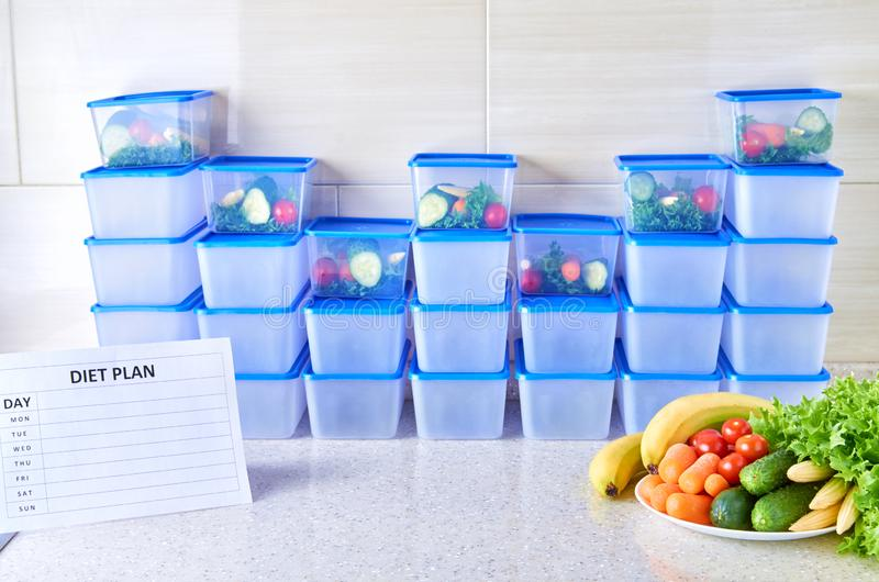 Un plan de la comida para una semana en una tabla blanca entre el sistema de los envases de plástico para la comida y la comida N fotos de archivo libres de regalías