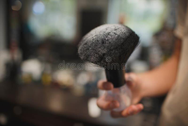 Un plan rapproché d'un accessoire de rasage sur un fond brouillé Une brosse noire dans la poudre de talc blanche Outils pour coup photographie stock
